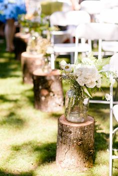 Log stumps with flowers down the isle