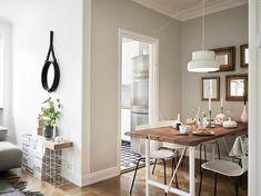 salon comedor, optimización de espacio, mesa de madera con piernas de metal blancas, pared decorada con espejos enmarcados, balcón pequeño, salón con alfombra y pilas de libros