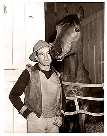"""George Monroe Woolf, nicknamed """"The Iceman"""", was a Canadian-born thoroughbred race horse jockey. An annual jockey's award given by the United States Jockeys' Guild is named in his honor. He became known for riding the people's champion Seabiscuit to victories in 1938. After his early death following a racing accident, Woolf was inducted into newly founded honorary institutions: the National Museum of Racing and Hall of Fame, Canada's Sports Hall of Fame and the Canadian Horse Racing Hall of…"""