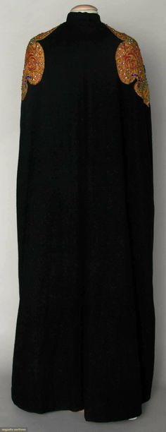 """Black wool, floor length, pale orange cartouche shaped shoulder appliques w/ gold soutache & bead & jewel Lesage embroidery, high band collar, double row of welted button holes at either side of opening, unlabeled except for shop label """"Importer Josephine Smith, Springfield, Mass"""", pale orange lining,"""