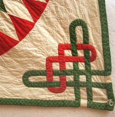 Celtic Knot corner on a red-and-green Sunburst quilt posted by Lisa at Stray Threads