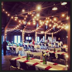 Rustic barn wedding. Burlap table runners, roses and baby's breath in recycled wine bottles. |  Baumann's Florist