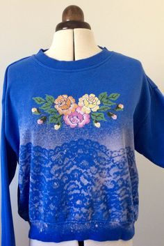Re-fashioned sweatshirt. Lace pattern made whith bleach and hand embroidered cross stich roses. Note: the placement of the embroidery should be higher....