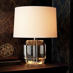 Clearly a gem, this prismatic lamp reflects light from every facet. Crystal glass is cut into a hefty geometric form that's multidimensional, but understated in its see-through minimalism. Oversized white cotton drum shade softens the glow.