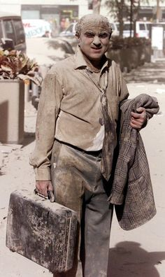 A man covered in dust walks in the street near the site of the World Trade Center towers in New York City, in this file photo taken early September 11, 2001.   (REUTERS/Shannon Stapleton-Files HB)