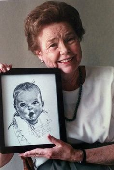"Ann Turner Cook is recognized the world over as the face of Gerber baby food. In 1928, Cook's neighbor, Dorothy Hope Smith submitted a charcoal sketch of then four month old Ann to a contest searching for ""a face to represent a baby food advertising campaign"" and won. Cook is now an 87 year old great-grandmother and proud of people's comparisons of their babies to her."