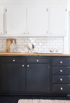 Charcoal colored bottom cabinets underneath white cupboards with a subway tile backsplash