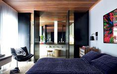 O teto revestido com ripas de cedro destaca-se no quarto, o qual se abre para o banheiro por meio de portas pivotantes pretas. Projeto do coletivo WHYDESIGN