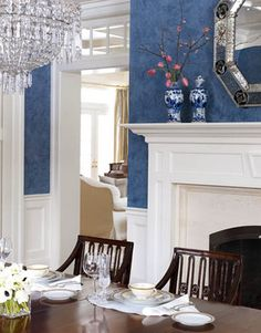Designed by Allison Caccoma, this beautiful, traditional dining room creates a dramatic contrast thanks to the creamy white moldings juxtaposed against the Prussian blue Venetian plaster walls.