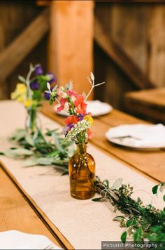 Simple, rustic wedding centerpiece idea - wildflower centerpieces with greenery garland -See more details on WeddingWire! {Picturist Photography}
