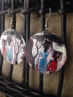 These beautiful earrings are made using recycled bottle caps that were hammered down and then hand painted by Ugandan artist, Davis Muwumba. They
