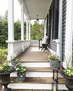 Beautiful wood porch with white railings gray siding and black shutters on this old house
