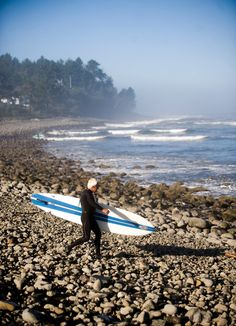 A surfer walks to the waves at Seaside's Cove.