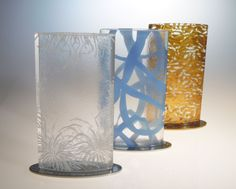 Glass flower vases for restaurant tabletops in delicate floral, contemporary blue and luxurious gold designs. By Glass Studio