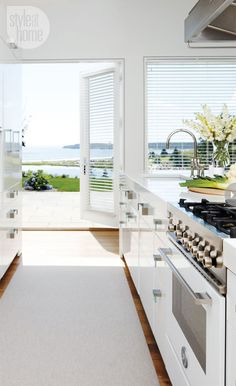 Modern beach cottage in Style at Home. Who wouldn't love to cook in this kitchen? The cabinets are a little sleek for me, but I love how everything looks fresh.
