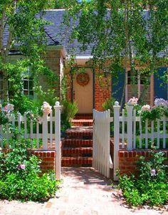 English garden with a white fence says, you're welcome to come in.