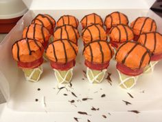 """Basketball Cupcakes.  Ice cream cone """"nets"""", with royal icing to pipe the net strings, melted red chocolate painted for the """"rim"""".  Cupcakes frosted with orange buttercream, then piped with melted mikl chocolate for the ball stripes."""