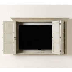 Now you see it, now you don't. When you're not watching, the Hughes TV Cabinet conceals your screen behind bi-fold French doors. Back is open to accommodate your TV mount. Our Cabinet holds a 55 screen (diagonal measurement); the interior space measures 30H x 48W x 5D. We recommend measuring the exact length, width and depth of your TV to ensure it will fit. Hughes TV Cabinet features:Double hinge doors fold back to wall for unobstructed viewingCable port at bottomAntique brass teardrop… Armoires Murales Tv, Tv Escondida, Entryway Storage Cabinet, Storage Shelves, Wall Shelves, Tv Plasma, Tv Wall Cabinets, Wall Mount Tv Cabinet, Tv Cabinets With Doors