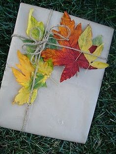wrapping presents with colorful autumn leaves Could also use paper snowflakes for Christmas presents