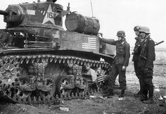 German soldiers inspect a knocked-out American Stuart tank.