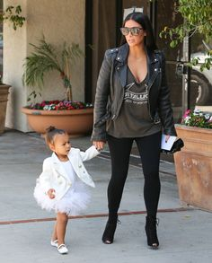 Kardashian rethinks the classic band T-shirt by looking to a style with a slouchy silhouette that shows off her ample cleavage. She tones down the sexy by wearing it with a heavy motorcycle jacket, leggings, and lace-up peep toe heels.   - HarpersBAZAAR.com