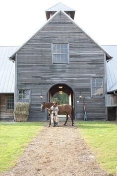 Charming barn.  weathered wood + tin roof + arched walk through