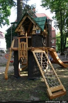 Wooden playhouse made from a huge tree trunk and poplar wood. It's a two-level playhouse. Children can climb up to the top using one of these three ways: steps, a wooden ladder or ropes. They can slide down from the upper floor, using the slide or the rope.