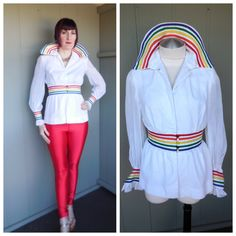 Vintage 1970s rainbow striped white puff sleeve blouse! Features a convertible wing collar with red, orange, yellow, green, and blue stripes like a rainbow arch. Snap at collar, bust, and waist. Sheer puff sleeves with matching rainbow stripes and 5 buttons and loops in each color. Ruffled cuffs. Matching rainbow stripes at waist with 5 buttons and loops in each color. Gathering above and below waistband. Body is fully lined, white sleeves are not, to maintain sheerness. Fabric is a cotton…