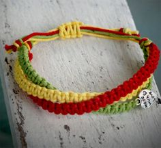 3Part Bracelet In Pastel Rasta Colors Made With by CaribbeanSpirit, $15.00 Material: cotton Charm: silvercolored metal Colors: rasta colors - red, yellow and green in pastel Length: adjustable with slip knot This braclet conteins three parts that are gently twisted and tied together in the ends.