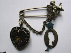 Este broche de imperdible lleva un charm de un corazón de color dorado viejo,  con una llave en su interior relleno de resina. Tiene también un colgante con la silueta de una señora retro, y un cupido.