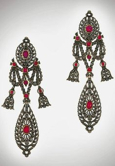 A pair of early 19th century ruby and diamond pendent earrings.  Each oval openwork surmount centrally-set with a cushion-shaped foil-back ruby and accented with old rose-cut diamonds all in closed-back settings, suspending a similarly-set garland and pear-shaped pendant, circa 1810, 10.5cm long, possibly Catalan