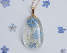 Nature inspired botanical necklace featuring forget me nots encased in clear resin - made by Floral Joy Jewelry