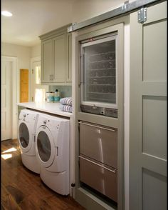 Laundry room with two drawer freezers and a wine frig hidden behind a closet door