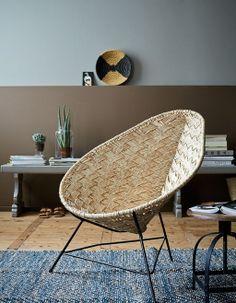 Wie niet van standaard houdt, weet deze opvallende loungestoel van gevlochten riet wel te waarderen.