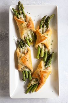 Bundles of asparagus, pancetta, and parmesan cheese baked in puff pastry.