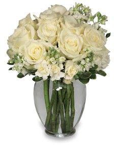 Ginger Vase  Foliage: Variegated Pittosporum  White Roses  White Stock  White Mini Carnations