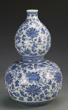 Chinese Blue and White Double Gourd Vase, China, 19th C., blue and white double gourd vase, Ruyi pattern at mouth rim and base, with a wave design border at the waist, densely decorated with interlocking floral pattern in blue shades, Qianlong mark on base. Height 12 1/8 in., Width 7 1/2 in.