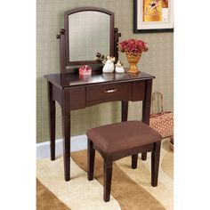 This three-piece vanity set with an espresso finish is a great addition to your bedroom or bathroom. A mirror, table with drawer and upholstered stool finishes this vanity set.