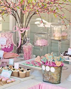 """Dessert table idea for a """"pink party"""". Rice krispie treats served from a shabby chic silver bucket. Cupcakes, cakes, candy canes, homemade candy served on white platters and glass cake dishes. Tree branches with pink, orange, and yellow flowers bundled together in a glass vase, with pink ribbon accent. #celebrate #event"""