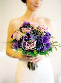 This gorgeous purple, violet, and lavender bridal bouquet features roses, anemones, and privet berries.