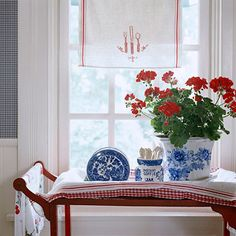 Decorating Patriotic.  Create temporary vignettes with red, white, and blue objects to update any room for the Fourth of July. Here a red teacart is topped with blue-and-white transferware, red-and-white linens, and a sunny geranium. Above, a red-and-white dishtowel adds flair to the window.