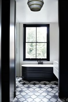 'Lantern' tiles from Popham Design add to the monochrome effect in the bathroom and dressing room. Interior design by Suzy Hoodless.