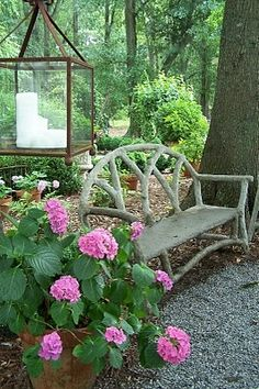 Pink geraniums, lantern and twig bench ~ lovely garden vignette