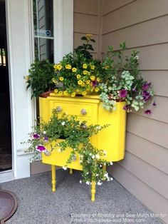 Bright yellow dresser filled with beautiful flowers in corner of front porch
