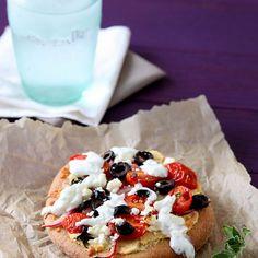 Greek Pita Pizzas Recipe Main Dishes with olive oil, pitas, red wine vinegar, salt, fresh oregano, purple onion, pitted kalamata olives, grape tomatoes, hummus, shredded mozzarella cheese, feta, sauce