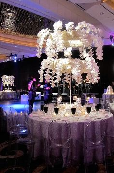 Round tables with Lucite chairs are topped with two-tiered arrangements of white phalaenopsis orchids and roses.