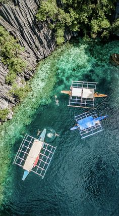 Drone photo of three banca boats in Coron Island, Philippines. Dramatic limestone cliffs, crystal clear water with varying shades of blue and a stunning interior or sacred lakes make this island a special place. Photo Location: Coron Island, Philippines by the Divergent Travelers Adventure Travel Blog. Click to see all of the Amazing Drone Photos of the Philippines at http://www.divergenttravelers.com/drone-photos-of-the-philippines/