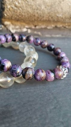 A strand of incredible, rare Siberian Charoite gemstone beads, averaging 7-8mm in diameter, display all the fabulous chatoyant violet, lavender and rich deep velvety purple hues that this stone is so admired for! Beads also contain black, brown and clear streaks and inclusions. In the center sits a Sterling Silver spiral wave accent bead.  This elastic bracelet fits most womens wrists up to 7 inches in circumference. Charoite comes from an area of Siberia once associated with political…
