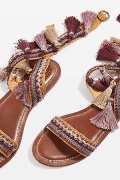 Jazz up your sandals collection with this fun fringed flat style. Featuring a cross-strap and adjustable ankle strap its rustic fringed design defines the look
