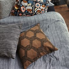 """Marimekko Sulhasmies Brown Throw Pillow Tying the knot. The phrase """"tying the knot"""" takes on a new meaning with Maija Isola's Sulhasmies (Groom) pattern. Simple and abstract, strands of black interlace to form a lattice-like motif on . Brown Throw Pillows, Home Decor Sale, Marimekko, Pillow Talk, Comforters, Sleep, Blanket, Living Room, Bedroom"""